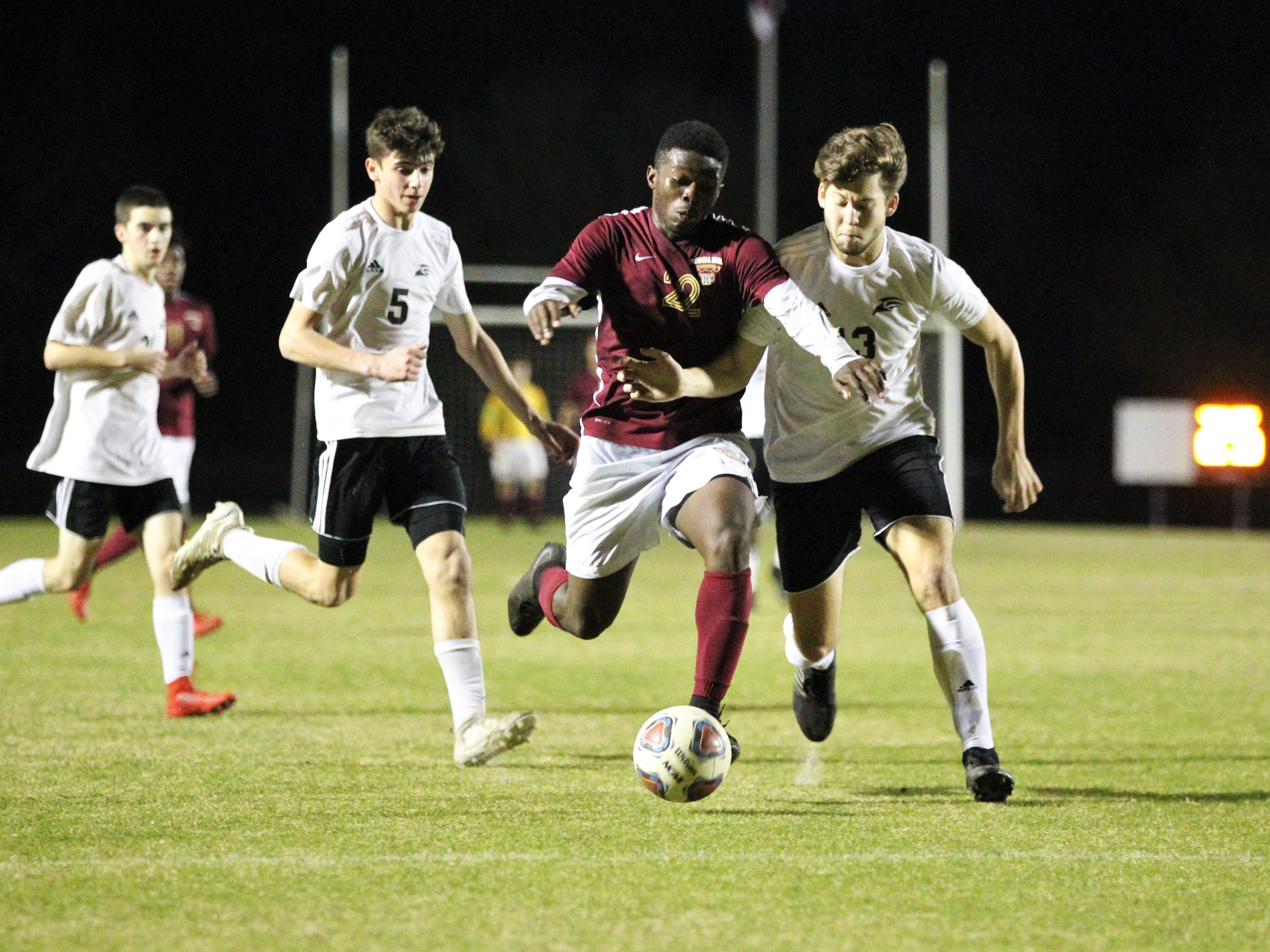 Florida High's Delali Simpson fights for a through ball as Florida High's boys soccer team beat South Walton 2-0 during a Region 1-2A quarterfinal on Feb. 6, 2018.