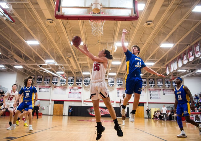 South Fork's Stone Jackson (center) goes under the basket to score in the first period as Martin County's Ryan Davis (right) tries to defend during the high school boys basketball game Wednesday, Feb. 6, 2019, at South Fork High School in Tropical Farms.