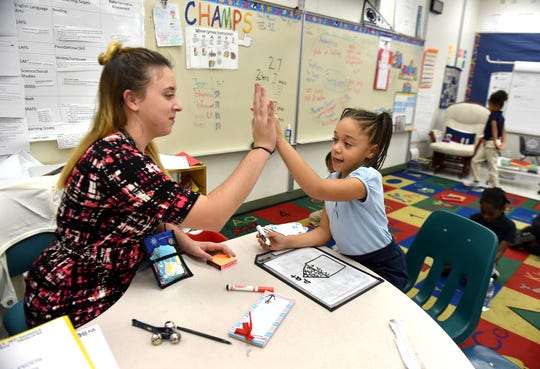 First-grade teacher Lisa Imperato celebrates the progression of student Timaiya Elkins Wimberly during word work lessons in this 2016 photo taken at Weatherbee Elementary School in Fort Pierce.