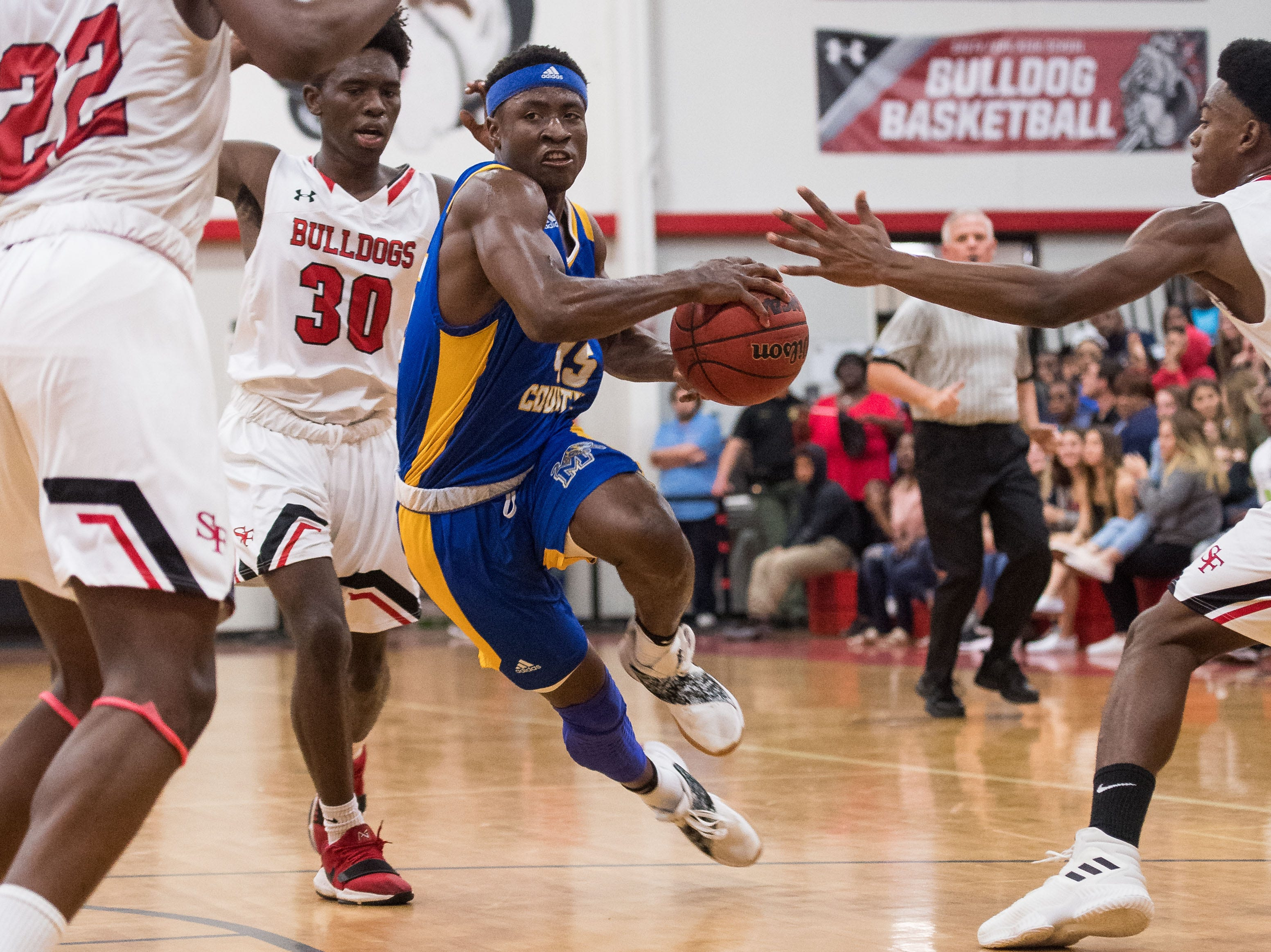 Martin County's George Johnson (center) drives with momentum to the basket but is fouled as South Fork's (from right) Darnell Johnson, Zach Lee and Nochly Rene defend during the second period of the high school boys basketball game Wednesday, Feb. 6, 2019, at South Fork High School in Tropical Farms.