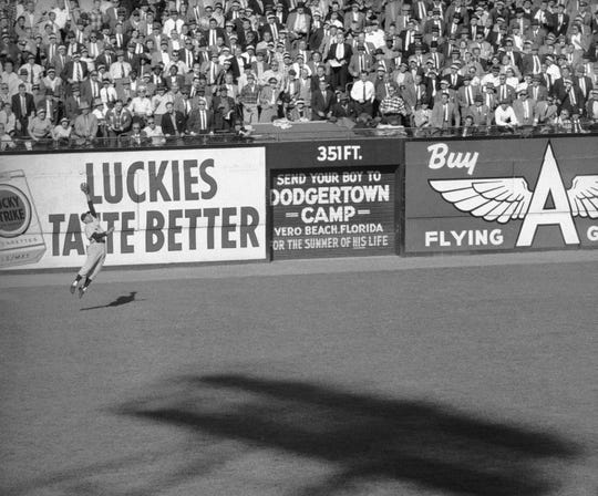 New York Yankees left fielder Enos Slaughter can't make the catch on Brooklyn Dodgers Jackie Robinson's winning hit in the bottom of the 10th inning during Game 6 of the World Series at Ebbets Field in New York, Oct. 9, 1956. Slaughter, battling the sun and shadows, charged and the ball sailed past him, hitting at the base of the left-center-field wall, scoring the game's only run. (AP Photo)