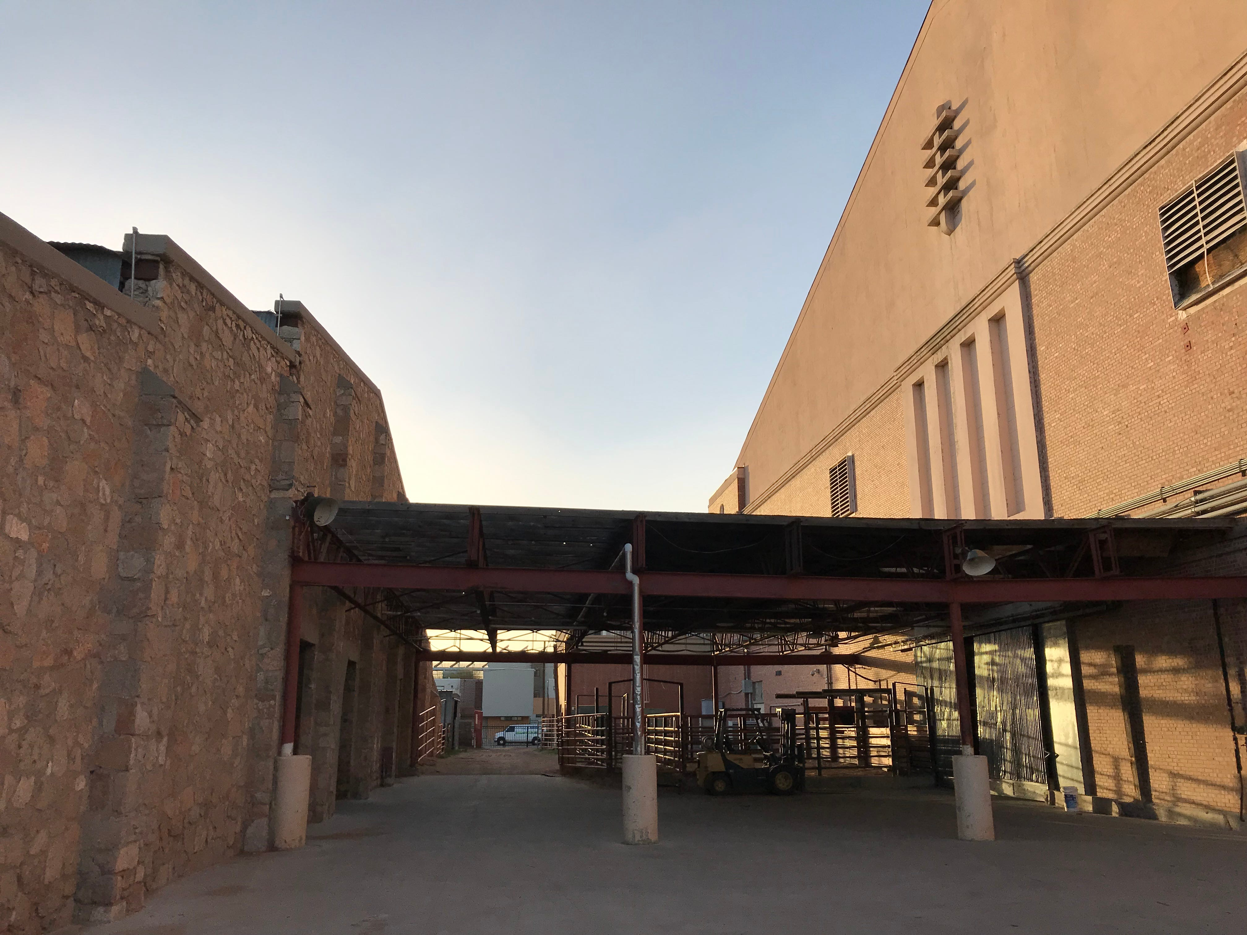 A rock building is connected to the rear of the El Paso County Coliseum by a covered walkway.