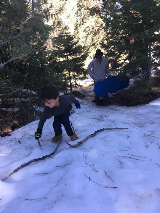 A Ventura family enjoys the snow near Mount Pinos.