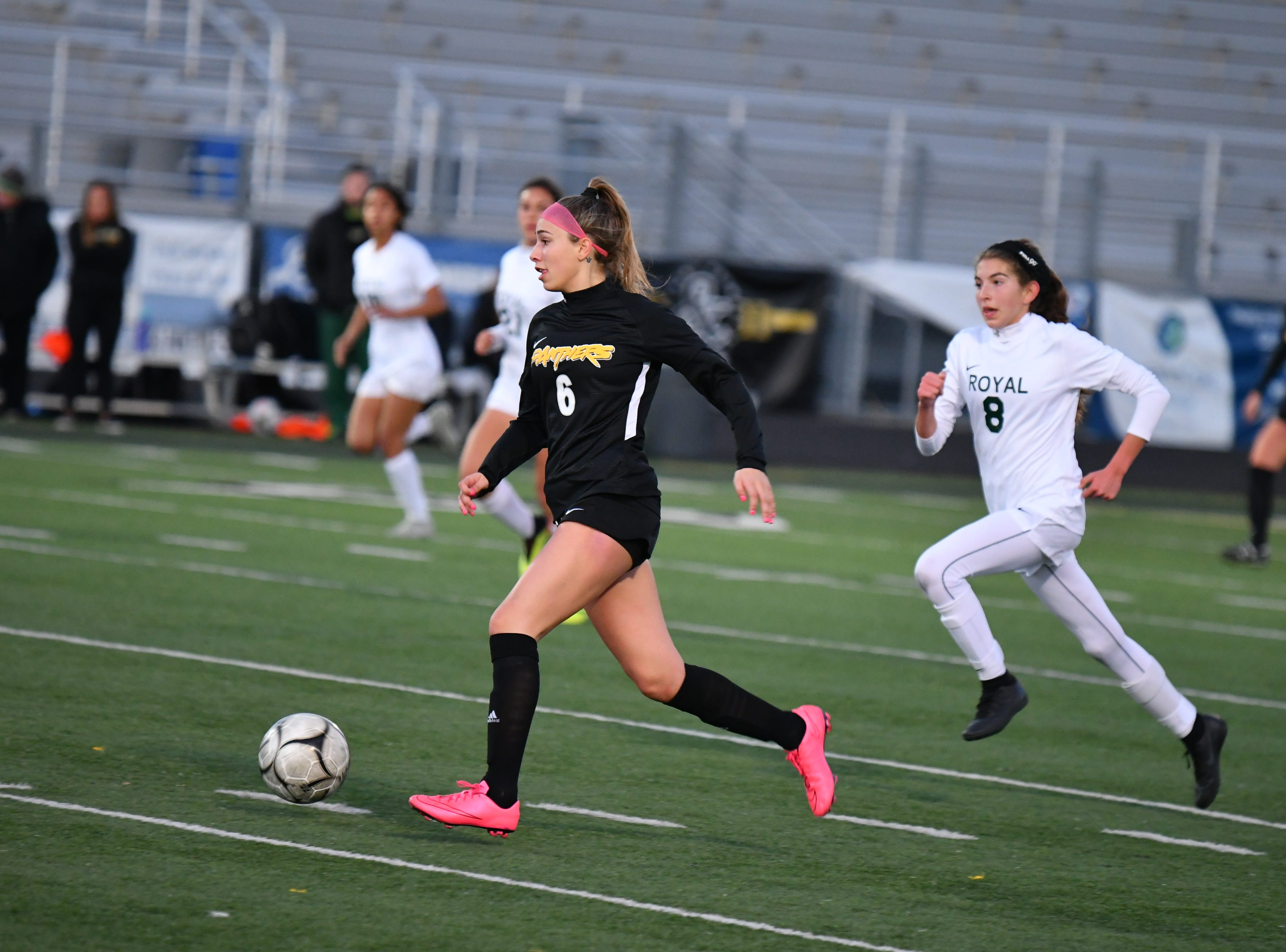 Newbury Park senior Fiona Marangola is chased by Royal freshman Avery Neri on Wednesday in the first round of the CIF-Southern Section Division 2 playoffs at Newbury Park High. Newbury Park won, 3-0.