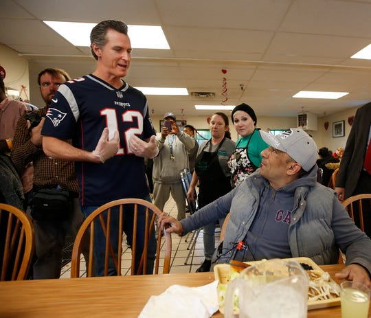 Wearing a jersey of New England Patriots quarterback Tom Brady, California Gov. Gavin Newsom, left, talks to Rico Alvarez, seated, while working the lunch service at Loaves & Fishes on Wednesday in Sacramento. Newsom lost a Super Bowl wager with Massachusetts Gov. Charlie Baker.