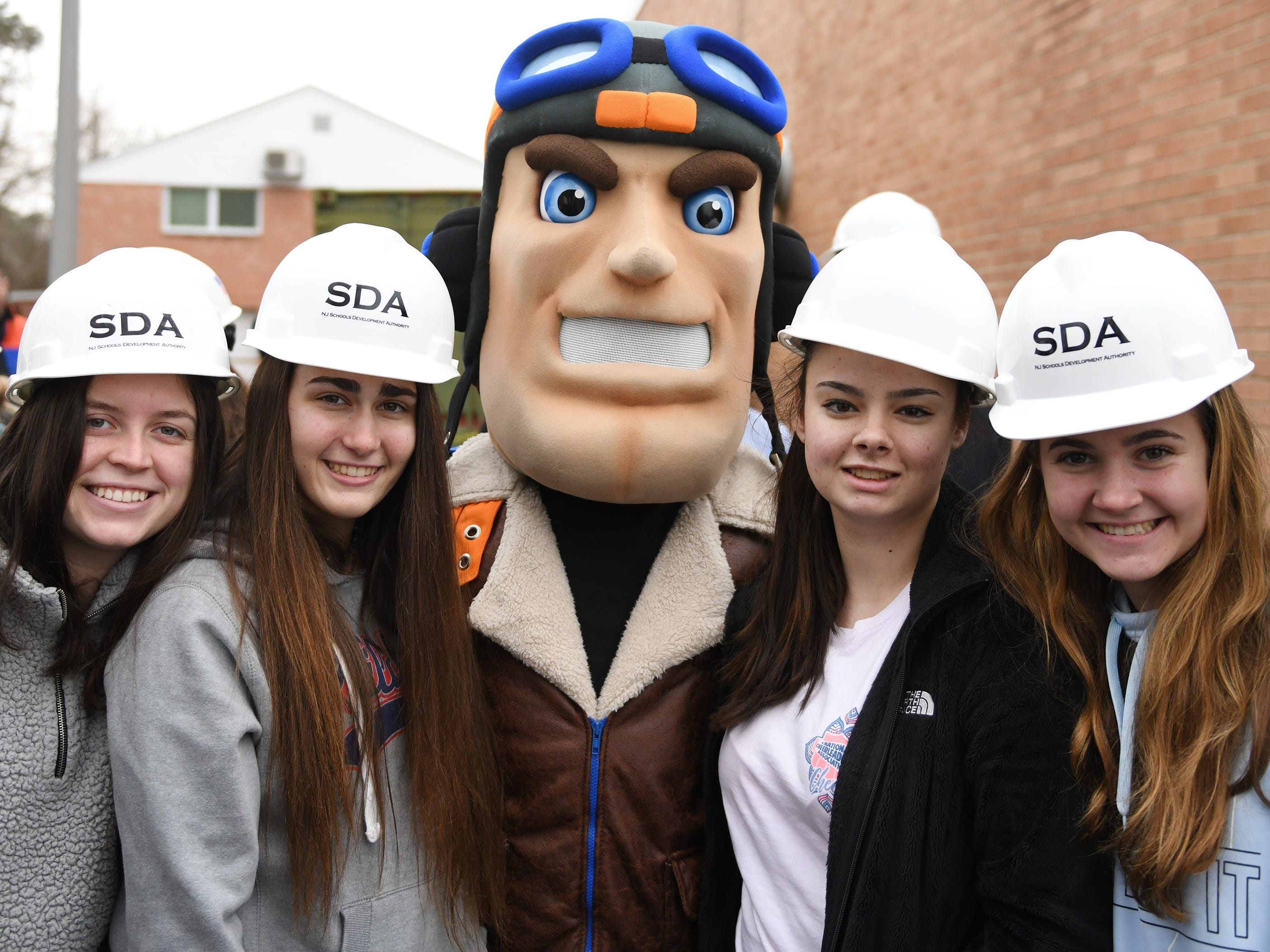 Maverick, the Millville High School mascot, joins students for a photo following a groundbreaking ceremony on Thursday, Feb. 7, 2019.