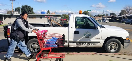 Visalia Code Enforcement collects two abandoned shopping carts on Santa Fe Street, as a man pushes a grocery cart on Feb. 2, 2019.