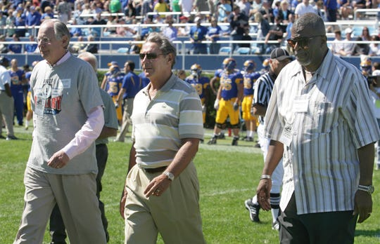 From left, Former U.S. Rep. Mike Castle; Joe Purzycki, and Nate Beasley head to midfield for the coin toss Saturday, Sept. 19, 2009 at Delaware Stadium.