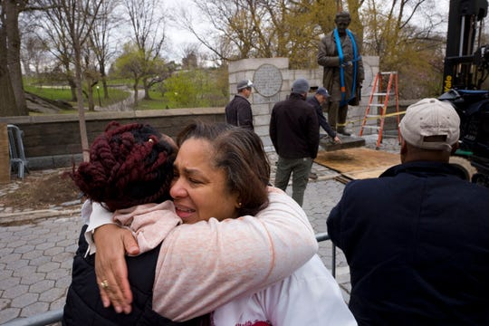 "FILE - In this Tuesday, April 17, 2018, file photo, Dr. Bernadith Russell hugs a friend as the statue of Dr. J. Marion Sims, is removed from New York's Central Park. Sims was known as the father of modern gynecology, but critics say his use of enslaved African-American women as experimental subjects was unethical. Russell, a gynecologist, said at the time she was in medical school, ""He was held up as the father of gynecology with no acknowledgement of the enslaved women he experimented on."" (AP Photo/Mark Lennihan, File)"