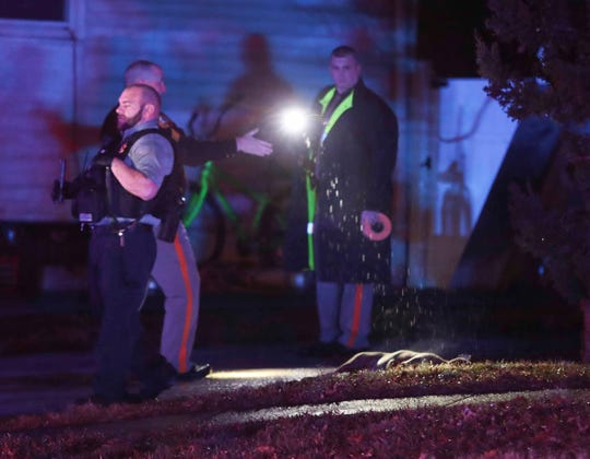 New Castle County police officers and animal welfare officers stand near a dead dog after it was shot and killed by a police officer. The dog was one of two pit bulls that attacked two women on Scottie Lane in Melanie Woods near New Castle about 6:45 p.m. Wednesday.