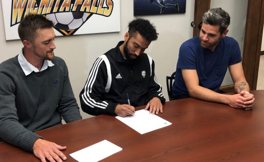 Former Rider and MSU standout Christian Okeke signed his contract Thursday to play indoor soccer with FC Wichita Falls. Coaches Brandon Swartzendruber (left) and Marcelo Campolino (right) are also on hand for the signing.