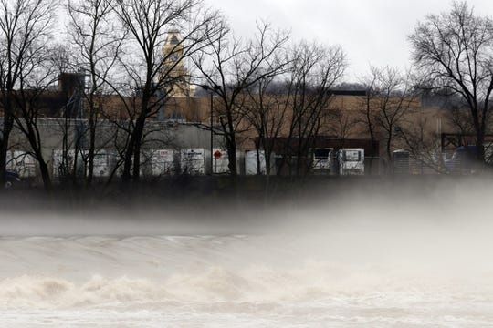 Fog shrouds the Muskingum River as it thunders over the dam at Zanesville Thursday afternoon.
