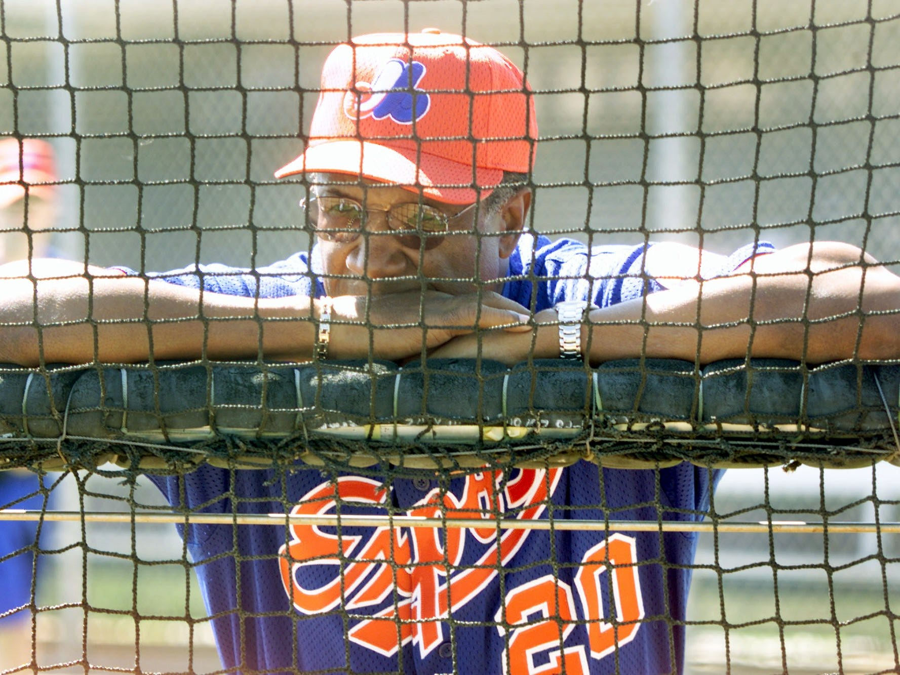 Montreal Expos manager Frank Robinson watches players batting practice during the first official day of training in 2002.
