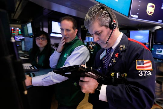Specialist Glenn Carell, center, and trader John Panin work on the floor of the New York Stock Exchange on Jan. 29, 2019.