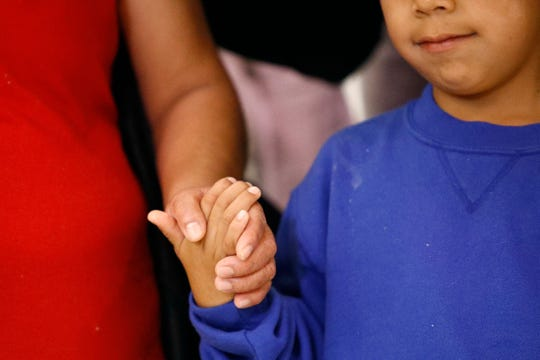 """A mother and son from Guatemala hold hands during a news conference on  June 22, 2018, following their reunion in Linthicum, Md., after being separated at the U.S. border under the Trump administration's """"zero tolerance"""" immigration enforcement policy."""