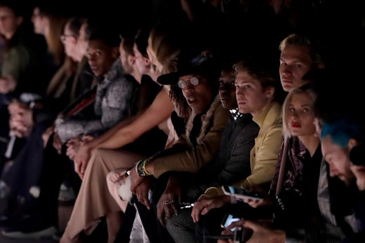 Carolina Panthers NFL quarterback Cam Newton, center wearing glasses, watches fashion from the Tom Ford collection modeled during Fashion Week, Wednesday, Feb. 6, 2019, in New York.
