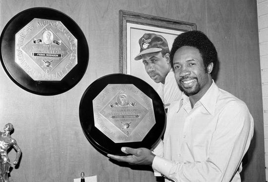 At his home in Los Angeles in 1971, Frank Robinson displays the trophies he received for being the Most Valuable Player in both the American and National Leagues.