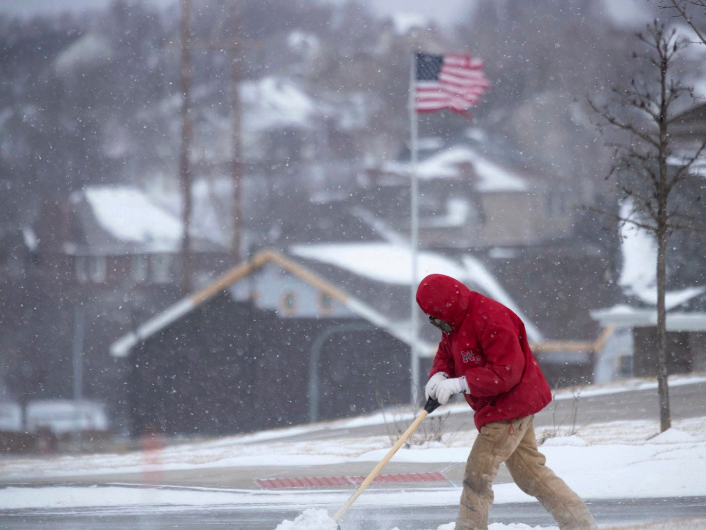 Ernesto Montoya clears snow in Papillion, Neb., as frigid temperatures hit the midwest on Feb. 7, 2019.
