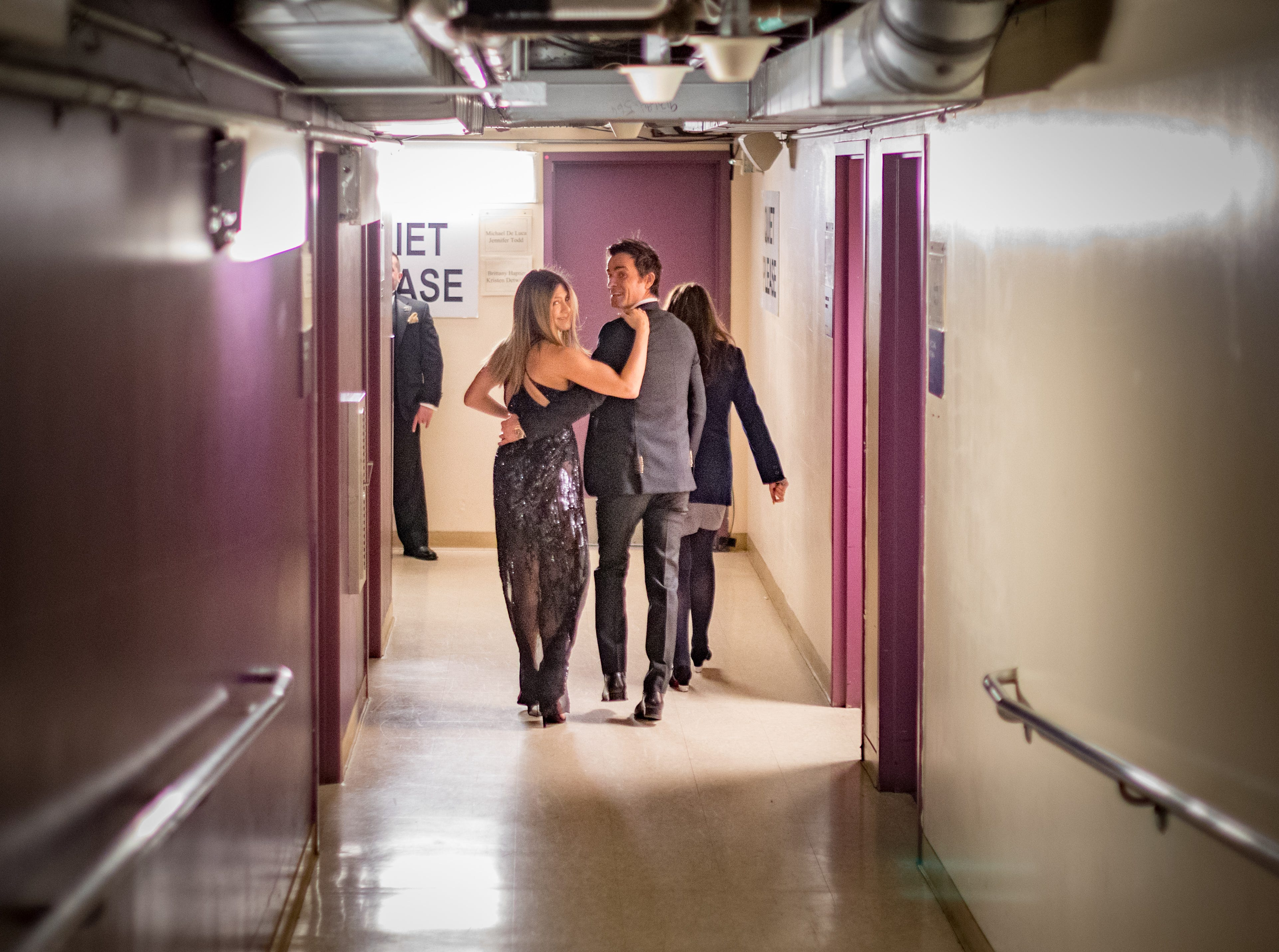After coming offstage at the Oscars, Aniston  was spotted canoodling in the hall with her husband.