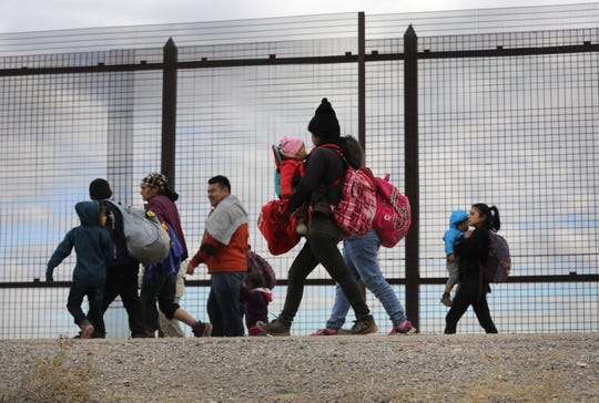 Central American immigrants walk along the border fence after crossing the Rio Grande from Mexico on February 01, 2019 in El Paso, Texas. The migrants turned themselves in to U.S. Border Patrol agents, seeking political asylum.