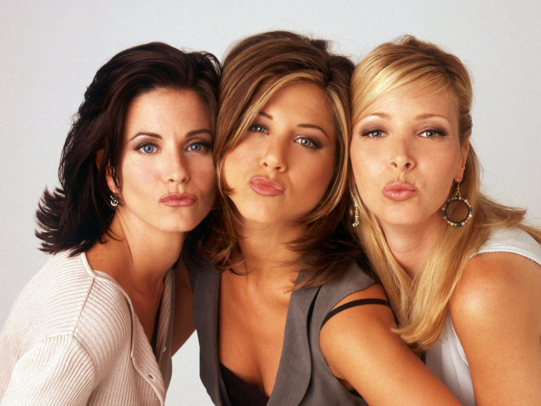 """The ladies of """"Friends"""" – Courteney Cox, left, Aniston, and Lisa Kudrow – pucker up in promotional photos for the show's second season, shot in August 1995."""