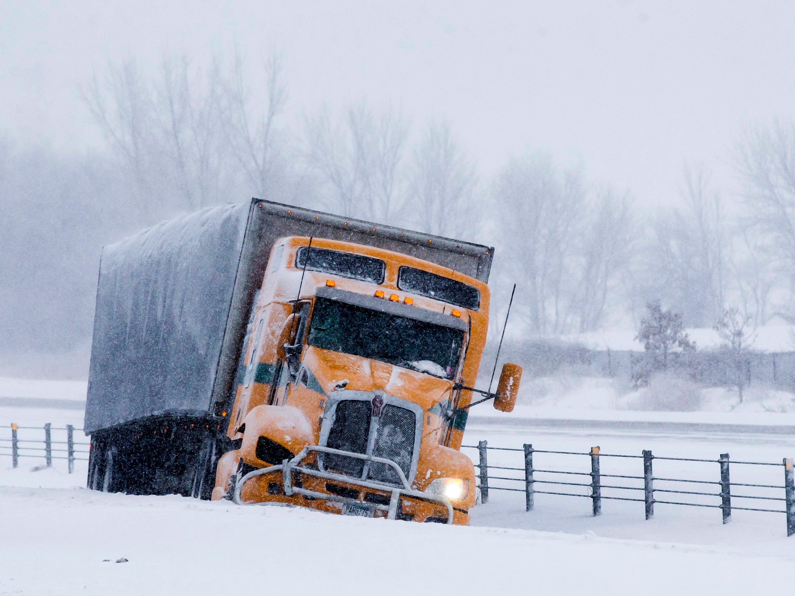 A semi truck sits in the median where a MnDOT snow plow rolled on its side on Highway 52 north of 75th Street on  Feb. 7, 2019, near Rochester, Minn.