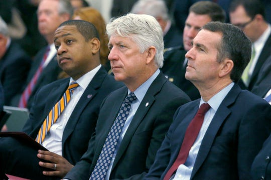 In this Dec. 18, 2017 file photo, from left, Lt. Governor-elect Justin Fairfax, Attorney General-elect Mark Herring and Governor-elect Ralph Northam listen as Virginia Governor Terry McAuliffe addresses a joint meeting of the House and Senate money committees at the Pocahontas Building in Richmond, Va.