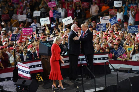 President Donald Trump is seen on stage with Rep. Mike Kelly and his wife Victoria during a rally at the Erie Insurance Arena in Erie, Pennsylvania on October 10, 2018.