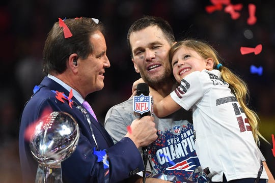Patriots quarterback Tom Brady (12) holds his daughter Vivian as he is interviewed by Jim Nance after Super Bowl LIII at Mercedes-Benz Stadium.