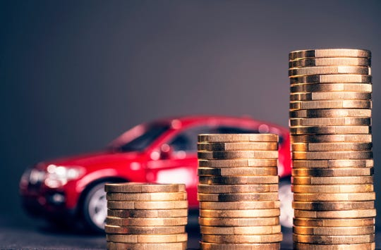 coins stacked in front of car money insurance auto