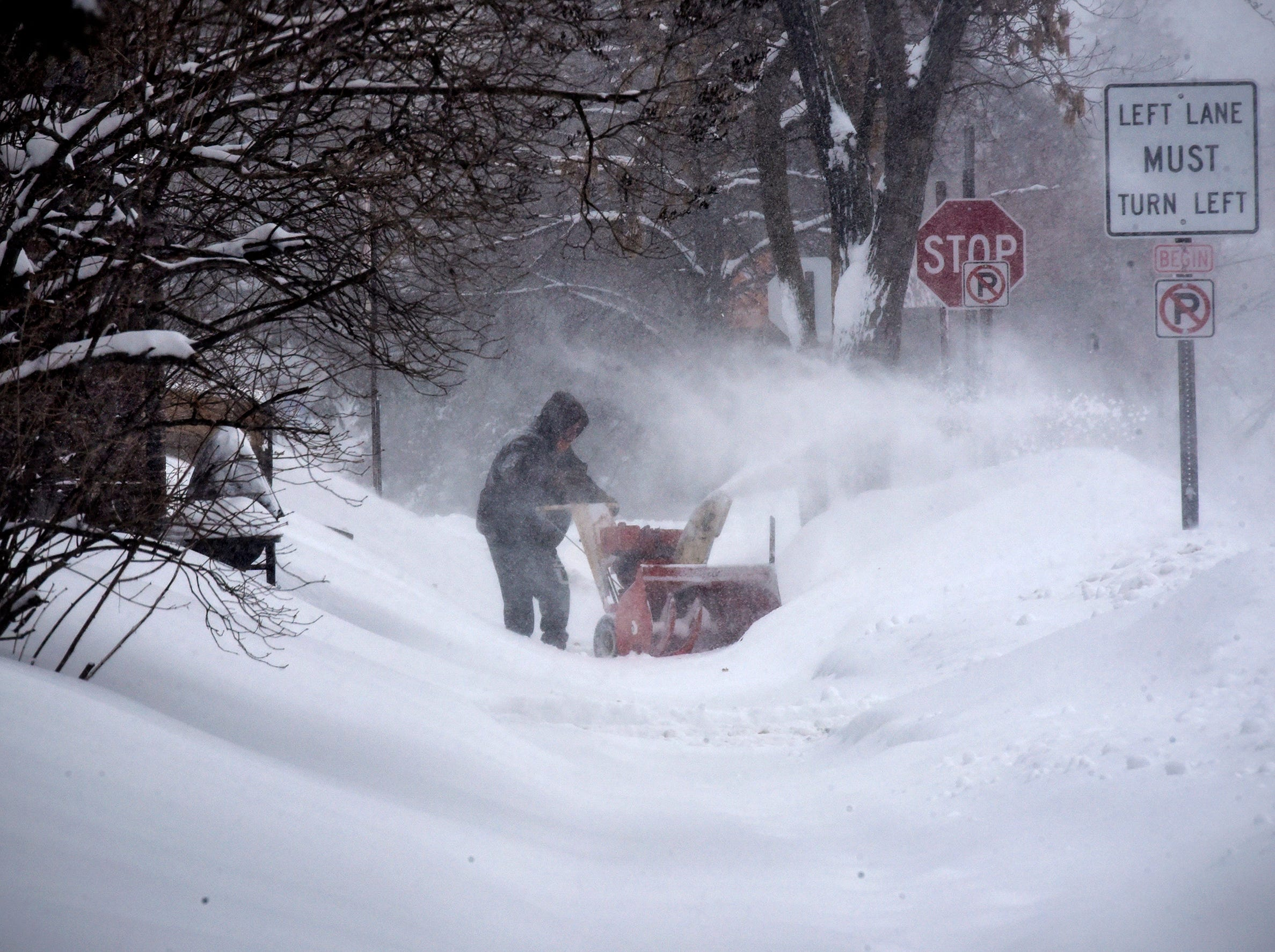 A resident clears a driveway as heavy snow continues to fall on Feb. 7, 2019, in St. Cloud, Minn.