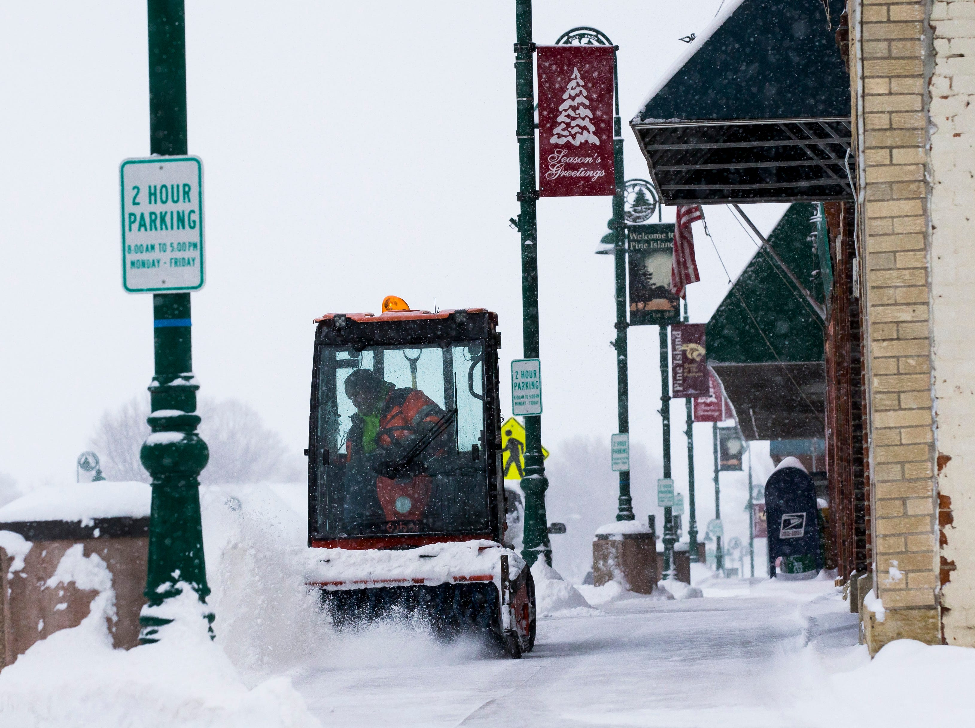Pine Island Public Works clears snow from a sidewalk in downtown Pine Island, Minn. on Feb. 7, 2019.
