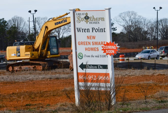 A sign for Wren Point new start homes coming soon, near road construction workers along Clemson Boulevard in Pendleton Friday. A subdivision is planned near the new infrastructure off of U.S. 76.