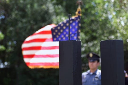 (REPORTER) 9/11/02 - Matawan - Matawan Police Department Patrolman Jennifer Paglia holds the American Flag by a memorial service featuring the reading of the each name of the victims of the Attacks of a year ago at Memorial Park.....JACK HOWARD/Staff Photographer