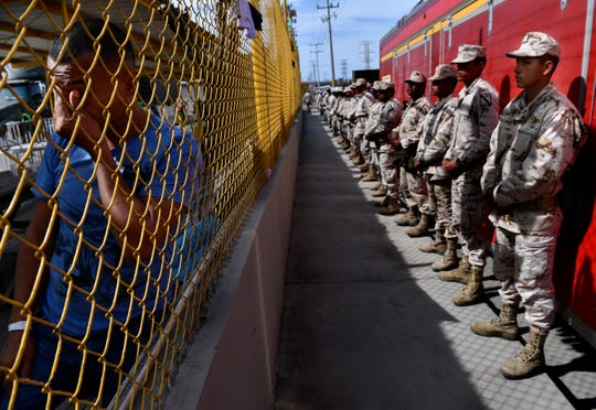 Aldo Hernandez rubs his eyes while leaning against the fence surrounding the Migrant Hostel in Piedras Negras, Mexico Thursday Feb. 7, 2019. At right, Mexican troops stand guard in front of the former factory. The caravan of 1,800 Central American migrants, consisting mostly of young adults and families with children, arrived here on Monday hoping to enter the United States in Eagle Pass, Texas.