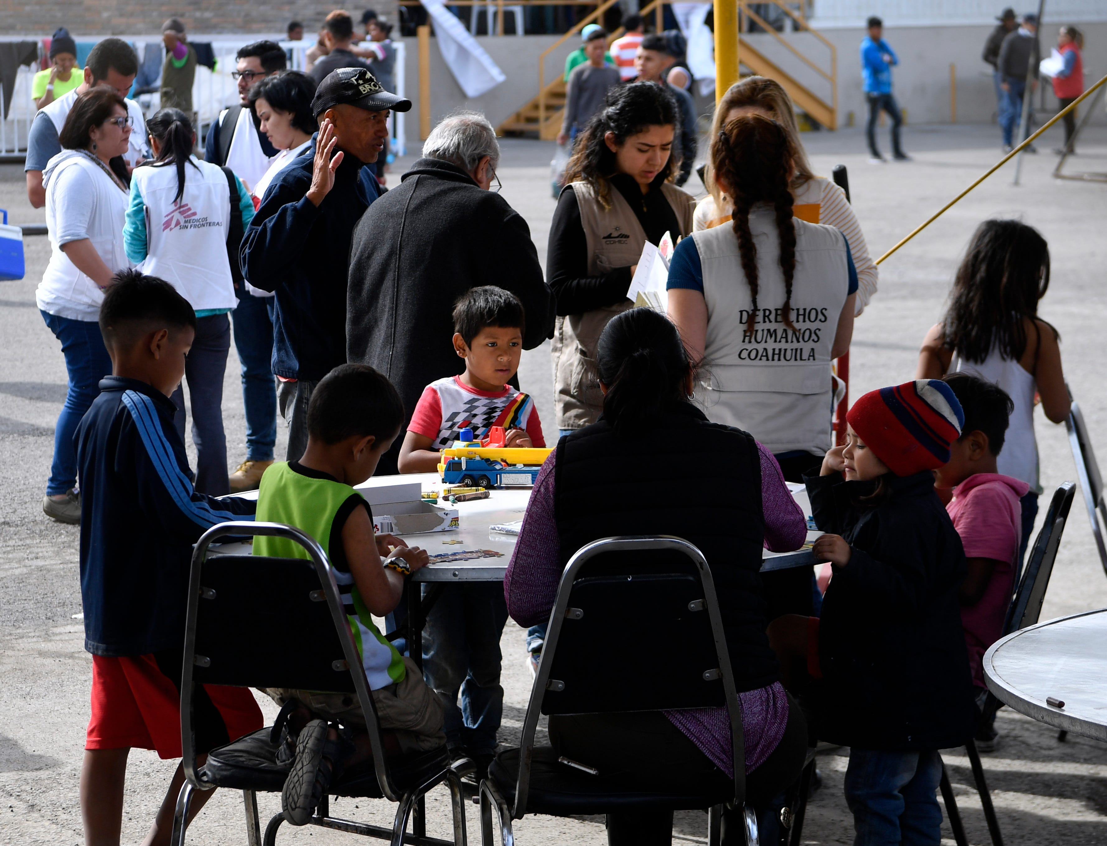 Children are led in an educational activity in the outdoor common area at the Migrant Hostel in Piedras Negras, Mexico, on Thursday, Feb. 7, 2019. About 1,800 young adults and families with children arrived here on Monday from Central America. Representatives from medical care missions like Doctors Without Borders were seen entering and exiting the compound, which is a former factory.