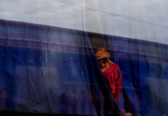 A Central American migrant who chose to self-deport looks out of a bus window and up at the policemen on the roof of the Migrant Hostel in Piedras Negras, Mexico on Feb. 7. The caravan of 1,800 young adults and families with children had arrived four days earlier.