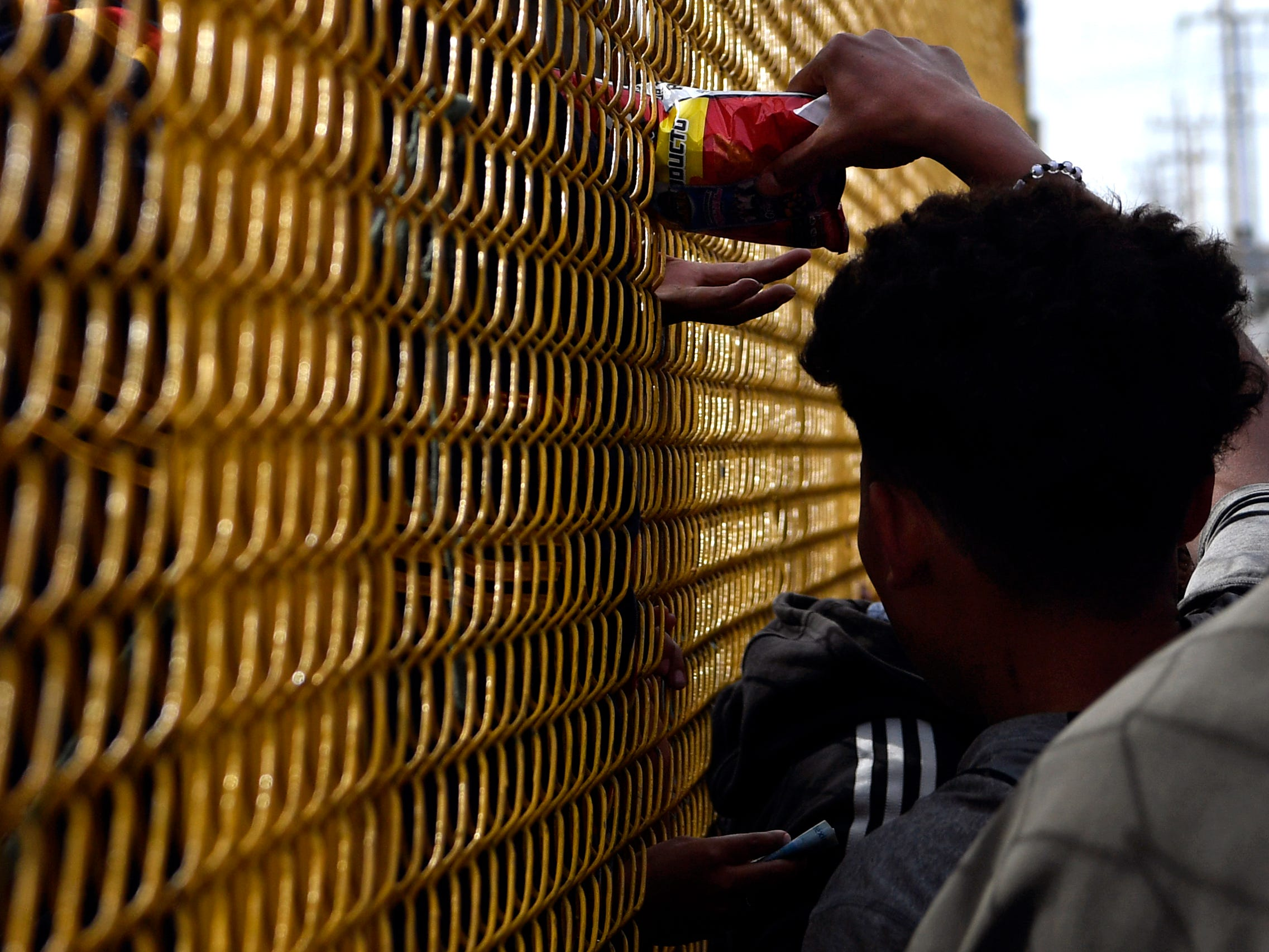 A man pushes a bag of potato chips through the chain link fence surrounding the Migrant Hostel Thursday Feb. 7, 2019 in Piedras Negras, Mexico. Some inside the compound were allowed to go outside under supervision and purchase snacks from a trailer parked in front of the former factory.