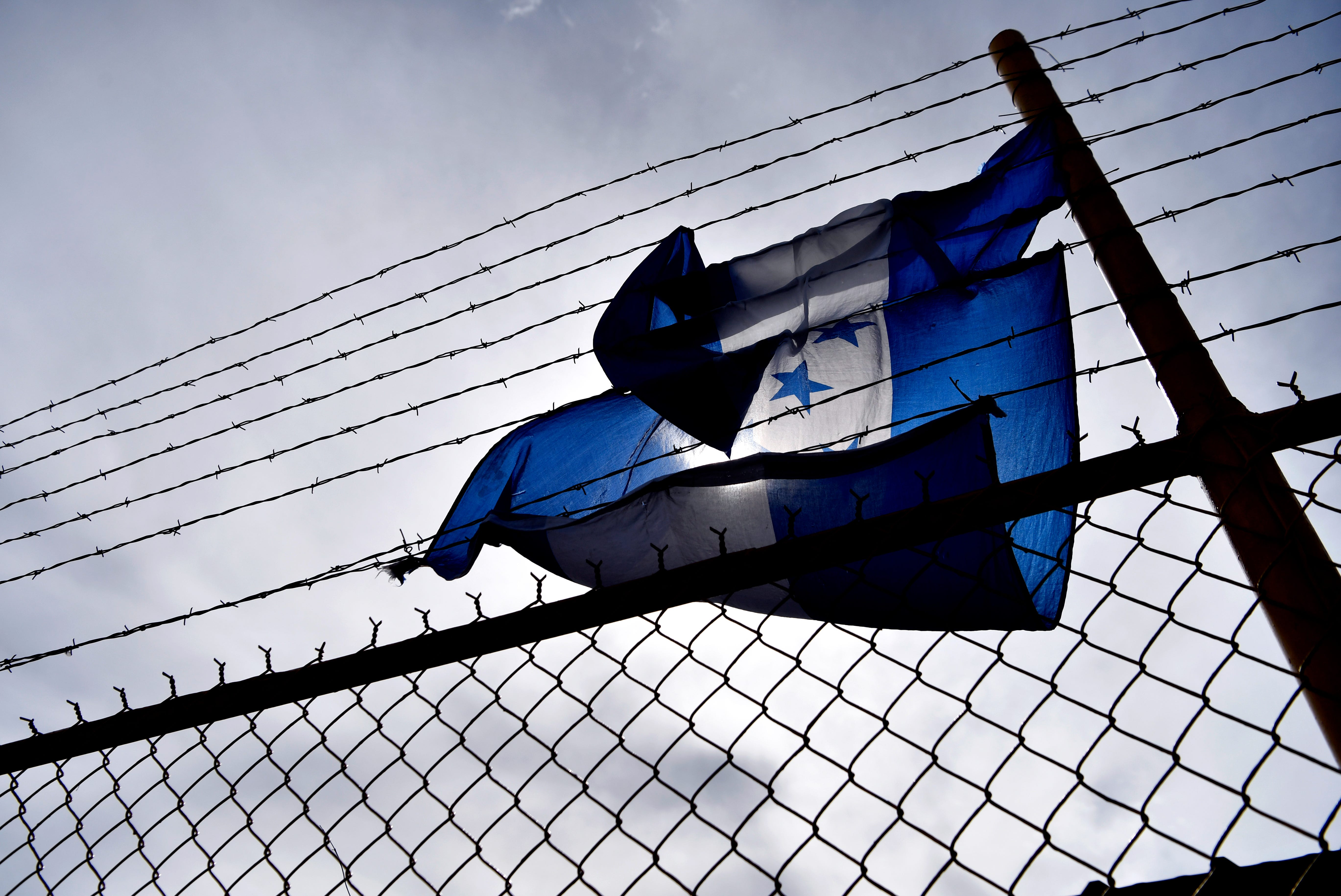 A Honduran flag is caught in the barbed wire surrounding the Migrant Hostel in Piedras Negras, Mexico Thursday Feb. 7, 2019. The former factory has been is a holding center for 1,800 Central American young adults and families with children. Many came from Honduras, hoping to escape the gang violence there which they say has taken over the country.