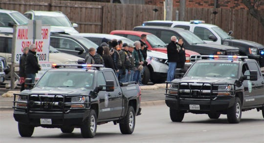Game warden vehicles pass onlookers standing at attention to honor fallen Border Patrol Agent Donna Doss as her funeral procession traveled Friday on Buffalo Gap Road.