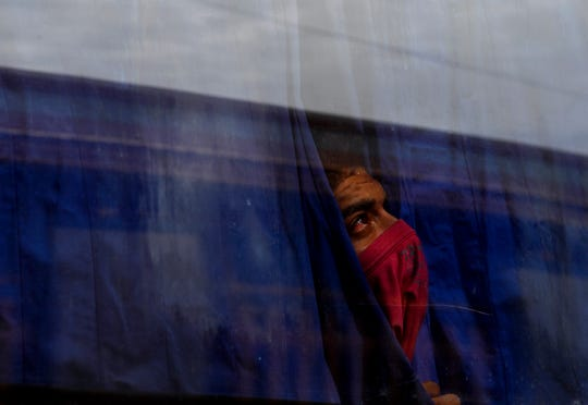A Central American migrant who chose to self-deport looks up at the policemen on the roof of the Migrant Hostel in Piedras Negras, Mexico Thursday Feb. 7, 2019. The caravan of 1,800 young adults and families with children arrived Monday but many expressed frustration at not hearing from U.S. officials on how they might be able to enter the United States.