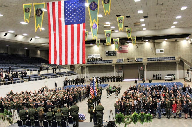 Family, friends and law enforcement from across Texas, including Border Patrol personnel, salute as a color guard followed by bagpipers march toward the casket of fallen Border Patrol agent Donna Doss at her memorial service Feb. 8, 2019, at the Taylor County Coliseum.
