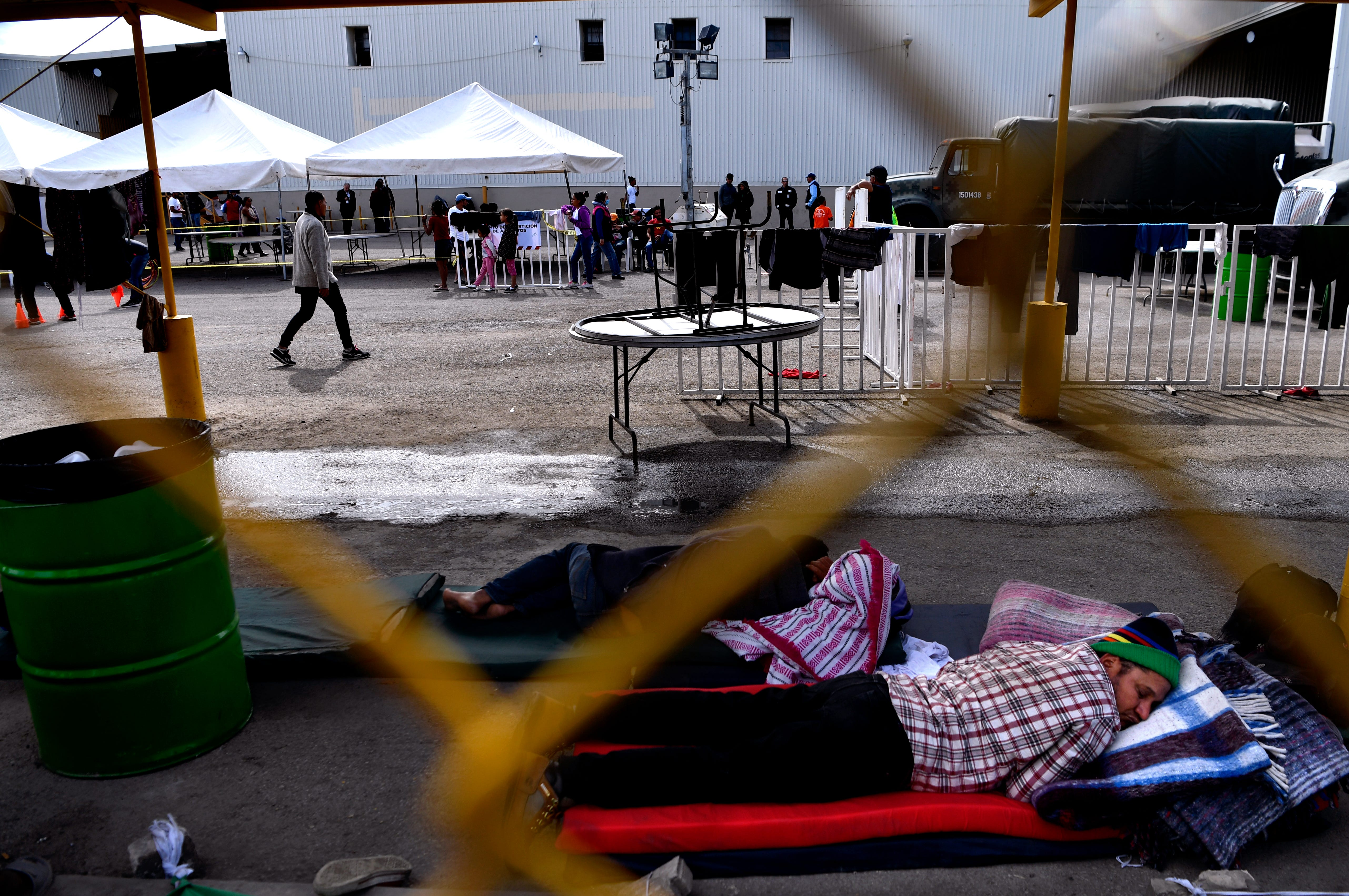 Men sleep on mattresses behind the chainlink fence surrounding the Migrant Hostel in Piedras Negras, Mexico Thursday Feb. 7, 2019. The former factory is said to have been converted into sleeping quarters inside, though some have set up tents made of blankets in the outdoor common area, too.