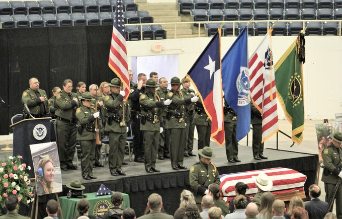 Flags, including the Border Patrol flag, far right, adorn the stage while the national anthem is sung Friday at the memorial service for fallen Border Patrol Agent Donna Doss at the Taylor County Coliseum.
