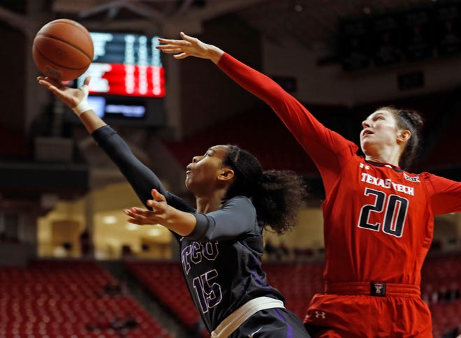 TCU's Jayde Woods (15) lays up the ball in front of Texas Tech's Brittany Brewer (20) during the second half Wednesday, Feb. 6, 2019, in Lubbock.