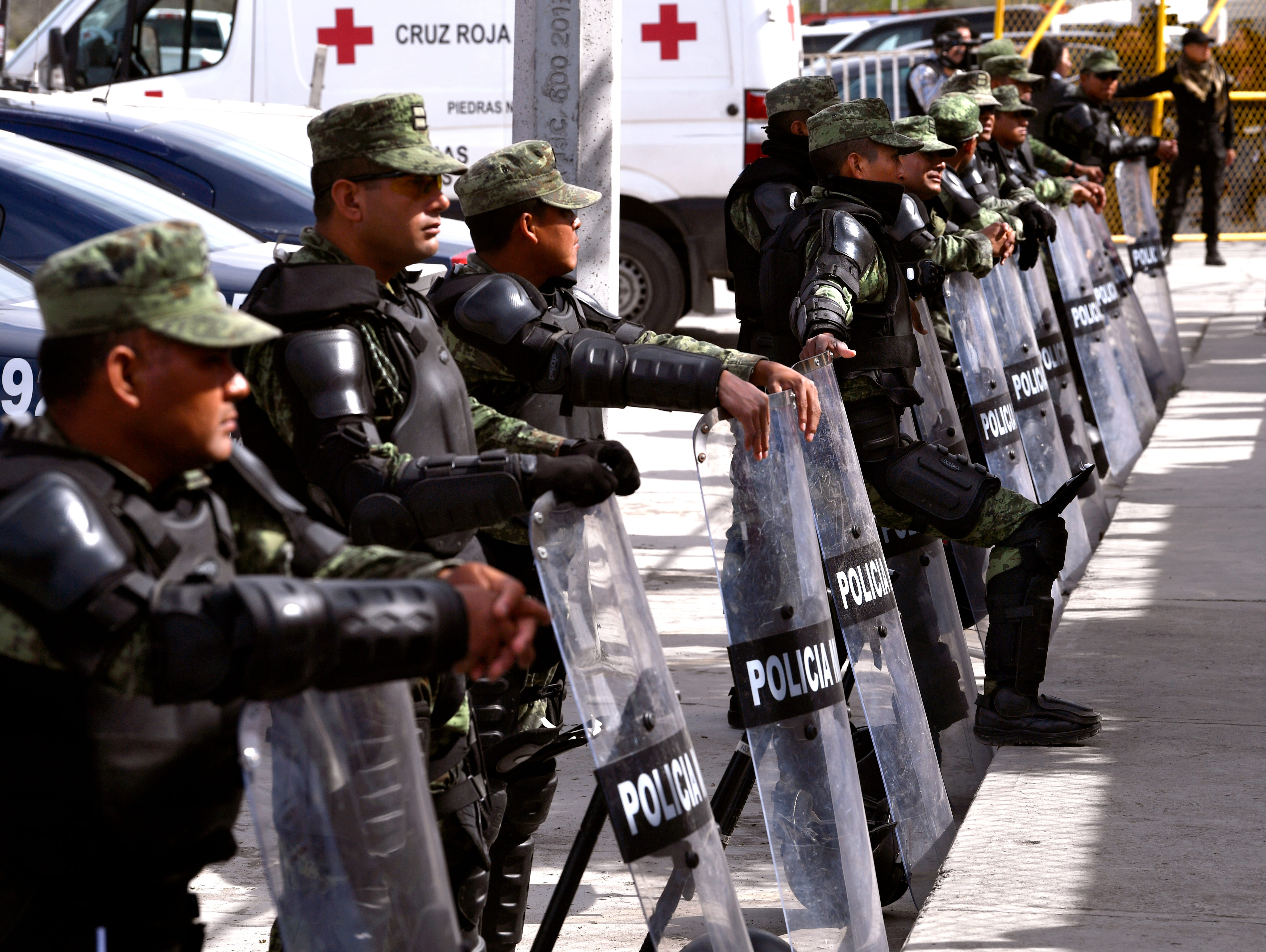 Mexican Federales stand outside the Migrant Hostel in Piedras Negras Thursday Feb. 7, 2019. The show of force included another line of officers with shields on the road behind these, plus truckloads of uniformed military troops also standing guard.