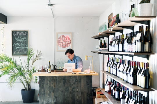 "John Hale works behind the counter at Crocodile Wine, his new shop downtown on Feb. 5, 2019. The shop, which has been open a little more than a month, sells all ""natural"" wines meaning the grapes are grown sustainably with no pesticides and with indigenous yeast."