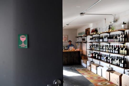 """John Hale works behind the counter at Crocodile Wine, his new shop downtown on Feb. 5, 2019. The shop, which has been open a little more than a month, sells all """"natural"""" wines meaning the grapes are grown sustainably with no pesticides and with indigenous yeast."""