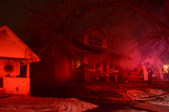 Bathed in the red lights from fire engines, a home on North Broad Street burns Friday morning.
