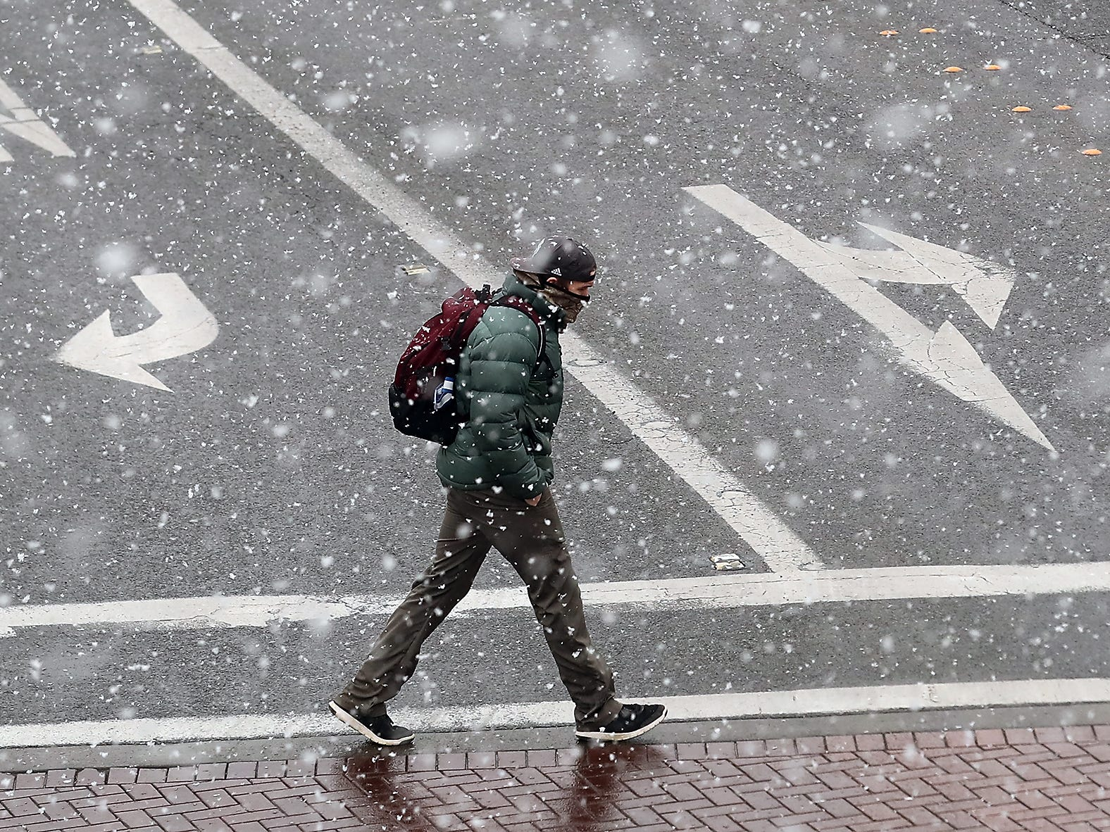 A pedestrian crosses Burwell at Pacific as snow falls in downtown Bremerton on Friday, February 8, 2019.